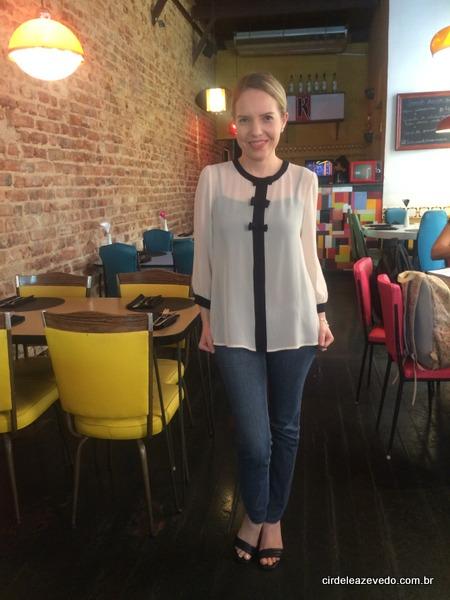 Eu usando blusa bege com detalhes preto no centro, gola e mangas, calça jeans e sandália de tira fina preta