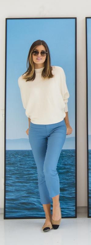 Camila veste tricô branco, calça azul e sapatilha bicolor nude com preto