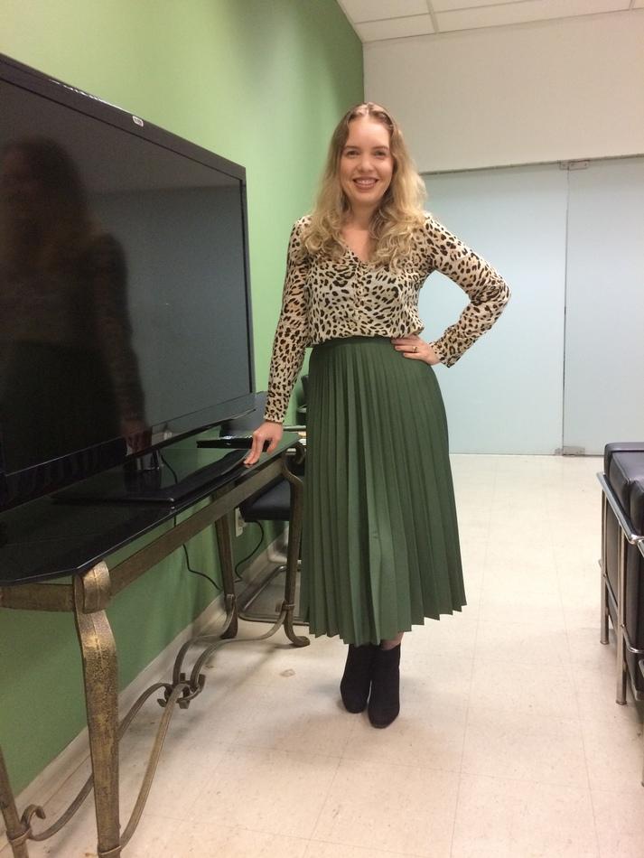 Saia verde plissada verde com blusa animal print de mangas compridas e bota de cano curto preta